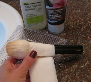 Wrapping the brush in folded toilet paper to retain brush shape.