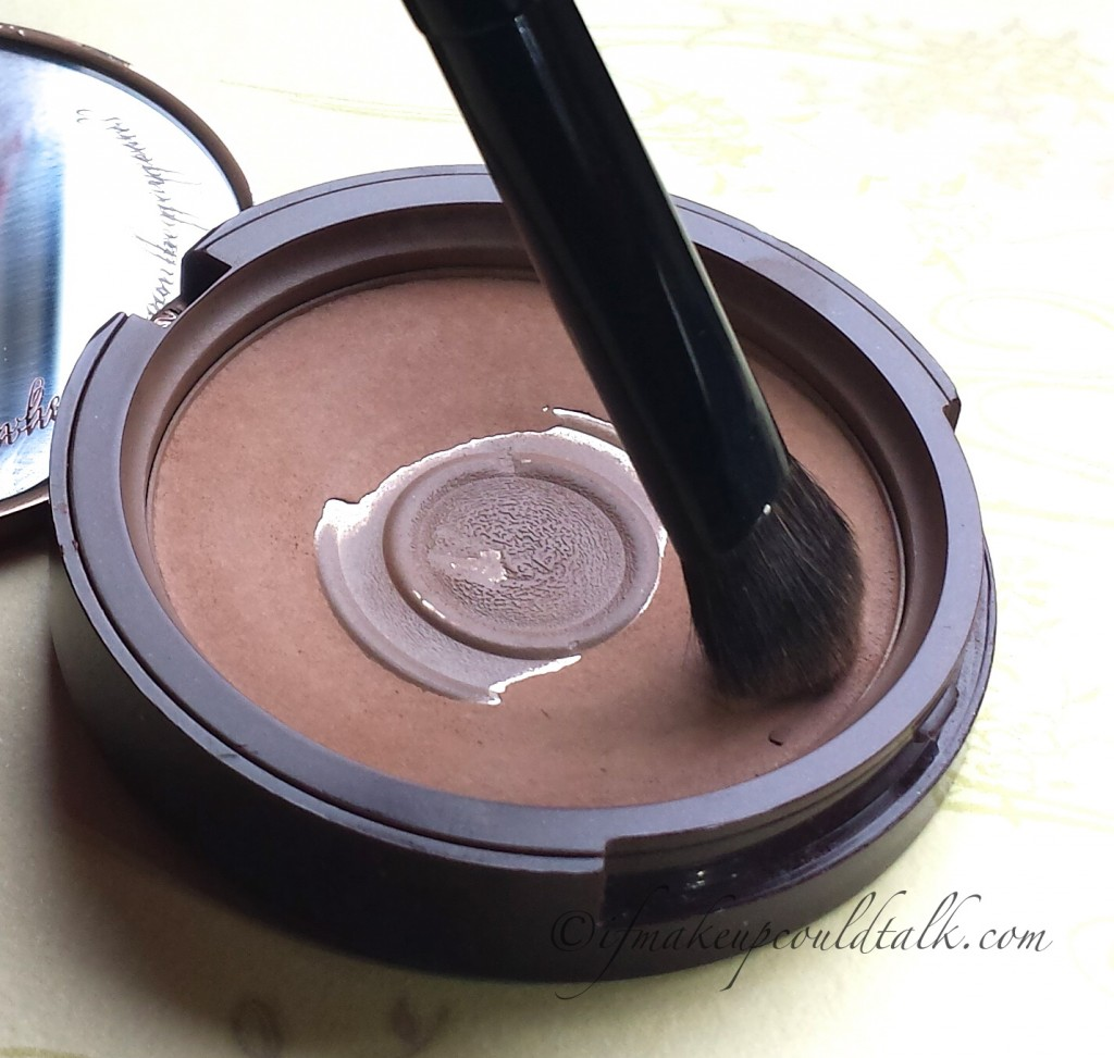 Chikuhodo Z-5 Eyeshadow Brush dipped into bronzer to apply color to the eye crease.